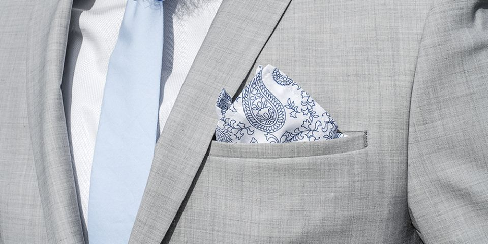 Man in a gray jacket with Shells pocket square and tie