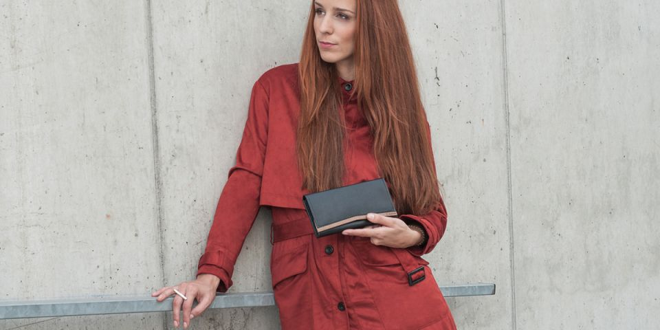 A woman with red hair in an orange coat holding a wallet made of wood and leather Caleo Woman Wallet